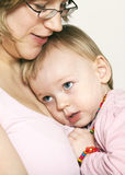 Baby girl cuddling up to her mother Royalty Free Stock Image
