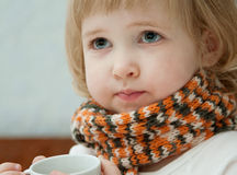 The baby girl with a cup of tea Royalty Free Stock Photos