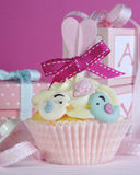 Baby girl cupcake with cute birds and ribbon closeup Stock Images