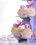 Baby girl cupcakes and booties on purple cupcake stand Royalty Free Stock Photos
