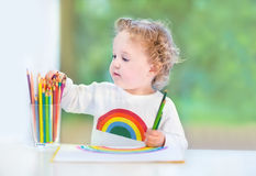 Baby girl with curly hair paiting with colorful pencils Royalty Free Stock Photography