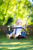 Baby girl with curly hair swinging in sunny park Stock Photo