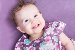 Baby girl with curly hair wearing a purple dress Royalty Free Stock Photo