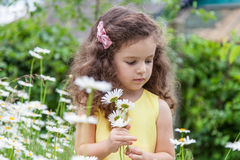 Baby girl with daisies outdoors Royalty Free Stock Photos
