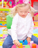 Baby girl in daycare. Cute adorable blond baby girl having fun in daycare, playing with colorful toys in playroom, happy healthy childhood stock image