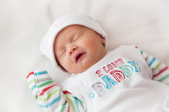 Baby girl sleeping. Baby girl (8 days old) taken in a very soft light (a light tent). Hat reads cute and top reads I love Daddy Stock Photo