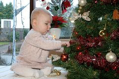 Baby girl decorating xmas tree Royalty Free Stock Photos