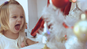 Baby girl delighted with the decorated Christmas tree Royalty Free Stock Images