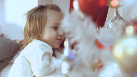 Baby girl delighted with the decorated Christmas tree Royalty Free Stock Photos