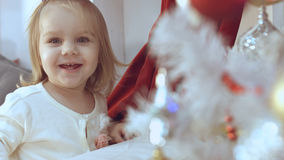 Baby girl delighted with the decorated Christmas tree Stock Image