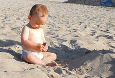 Baby girl discovers shell on the beach Royalty Free Stock Image