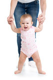 Baby girl doing first steps with help of mother Royalty Free Stock Images