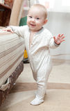 Baby-girl is doing her first steps. Royalty Free Stock Photography