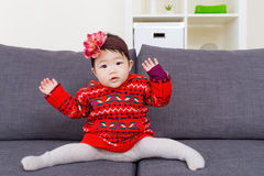 Baby girl doing legs splits on sofa Royalty Free Stock Photos