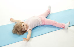 Baby girl doing sport exercises lying on the floor Stock Photography