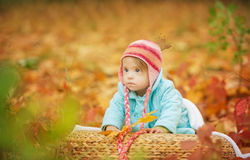 Baby girl with Down syndrome is resting in autumn forest Stock Photo