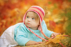 Baby girl with Down syndrome is resting in autumn forest. Baby with Down syndrome is resting in autumn forest Stock Photography