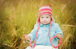 Baby girl with Down syndrome sitting in autumn park. Beautiful girl with Down syndrome sitting in autumn park Royalty Free Stock Photo