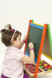 Baby girl drawing on black board with chalk. Isolated on white background Stock Photography