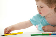 Baby girl drawing with colorful felt-tip pens Royalty Free Stock Image