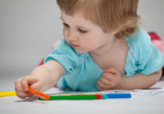 Baby girl drawing with colorful pencils Stock Images