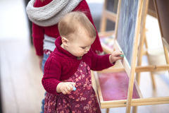 Baby girl draws chalk on  blackboard in children's area  shoppin Royalty Free Stock Images
