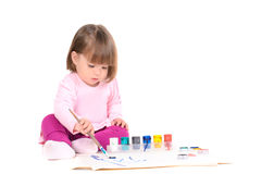 Baby girl draws by paints Stock Images