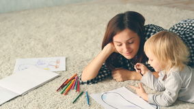 Baby girl draws a picture with pencils. Mother hugs and kisses her. stock video footage