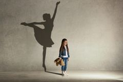 Baby girl dreaming a dancing ballet on the stage. Childhood concept. Baby girl dreaming about dancing ballet. Childhood and dream concept. Conceptual image with stock photo