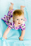 Baby girl in a dress creeps on the blue coverlet Royalty Free Stock Photos