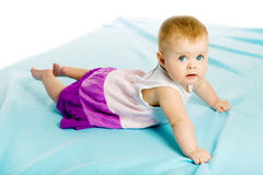 Baby girl in a dress creeps on the blue coverlet Stock Photography