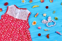 Baby girl dress flower print. Natural casual dress and head wrap for little girls, sweets, blue wooden background Stock Photography