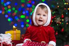 Baby girl dressed as Santa Claus at Christmas tree Royalty Free Stock Image
