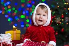 Baby girl dressed as Santa Claus at Christmas tree Royalty Free Stock Image