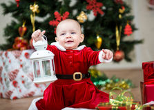 Baby girl dressed as Santa Claus at Christmas tree Royalty Free Stock Photo