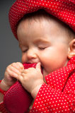 Baby girl dressed in a red dress eating a shoe Royalty Free Stock Photography