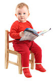 Baby girl dressed in red sitting on chair reading Stock Photography