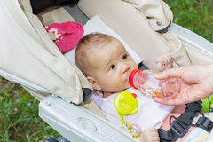 Baby girl drink water. Cute baby girl drink water of bottle Stock Photo