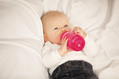 Baby girl drinking from baby bottle Royalty Free Stock Images