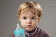 Baby girl drinking her milk in a baby bottle Royalty Free Stock Photos