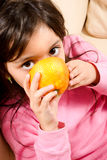 Baby girl drinking juice direct from an orange Stock Photos