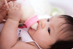 Baby girl is drinking milk Royalty Free Stock Images