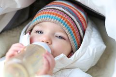 Baby girl drinking milk from bottle Royalty Free Stock Images