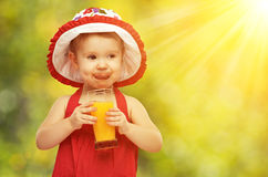 Baby Girl Drinking Orange Juice In The Summer Royalty Free Stock Photography