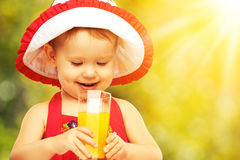 Baby girl drinking orange juice in the summer Royalty Free Stock Photos
