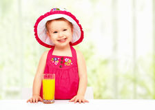 Baby girl drinking orange juice in the summer Royalty Free Stock Image