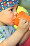 Baby boy drinking water. Close-up of baby boy drinking water herself from a bottle stock image