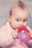 Baby girl drinking water from the red plastic bottle Stock Photo