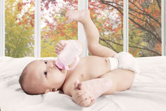 Baby girl drinks milk bottle Royalty Free Stock Images