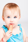 Baby girl eat biscuit Stock Images